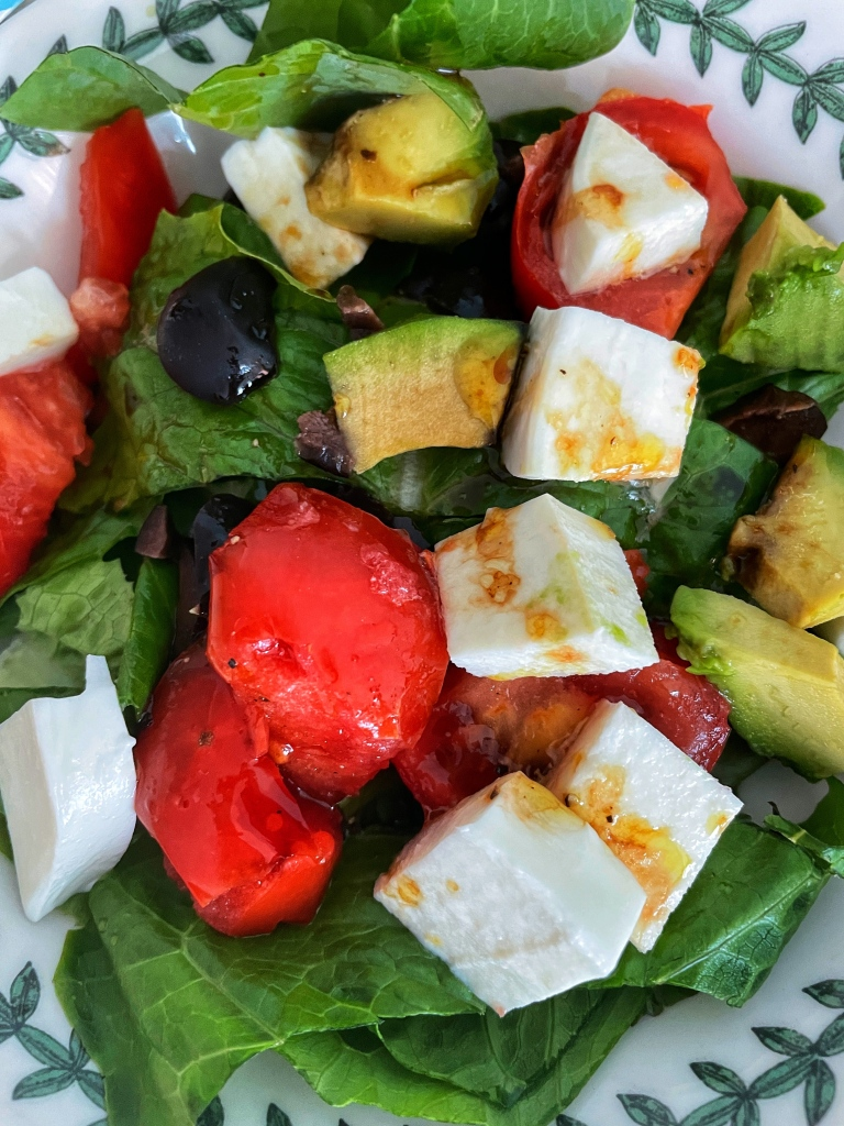 Salad with greens, mozzarella tomatoes, avocado and olives, topped with olive oil and balsamic vinegar
